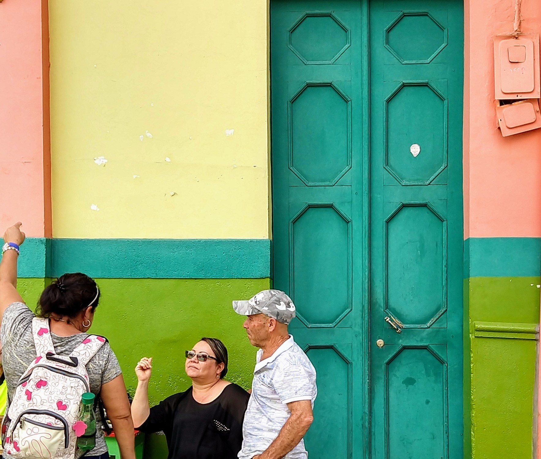 Jardin locals chat in front of a colorful house